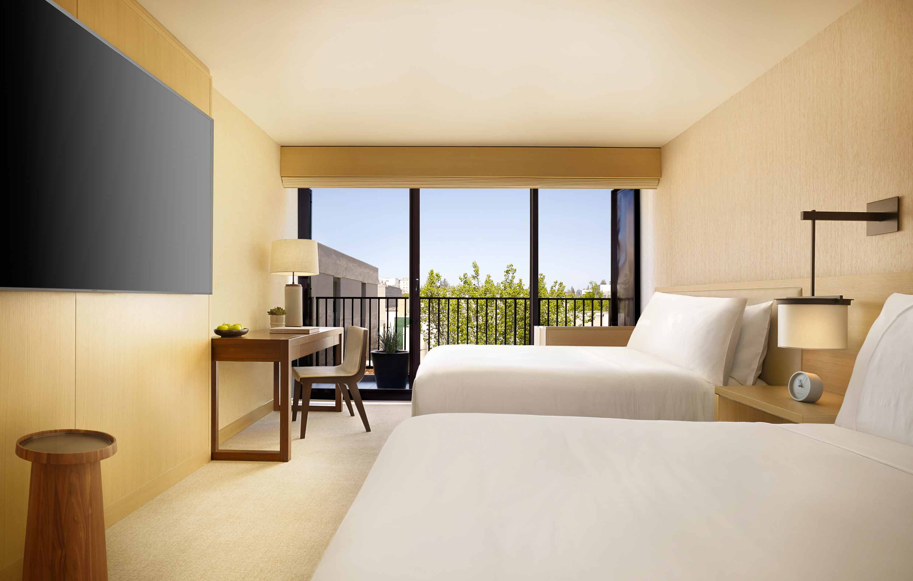 Room with two beds, desk and sliding glass door to balcony