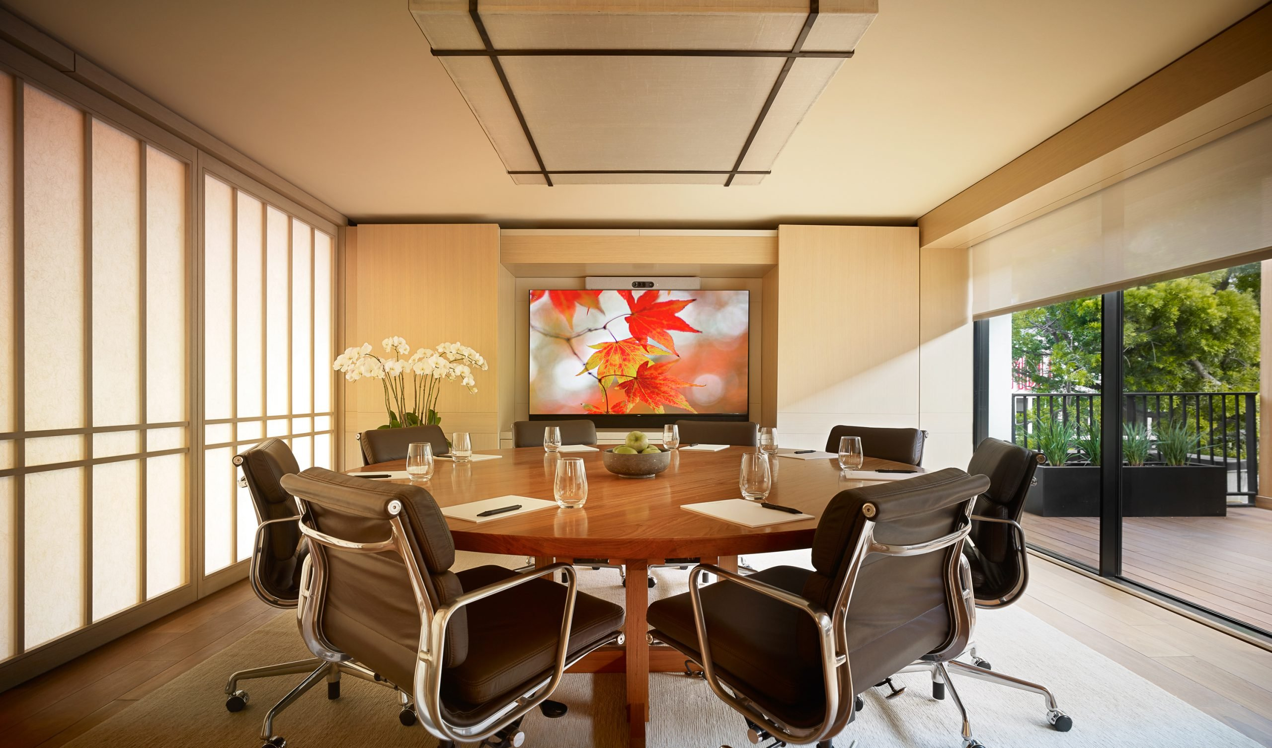 boardroom with round table and television on wall