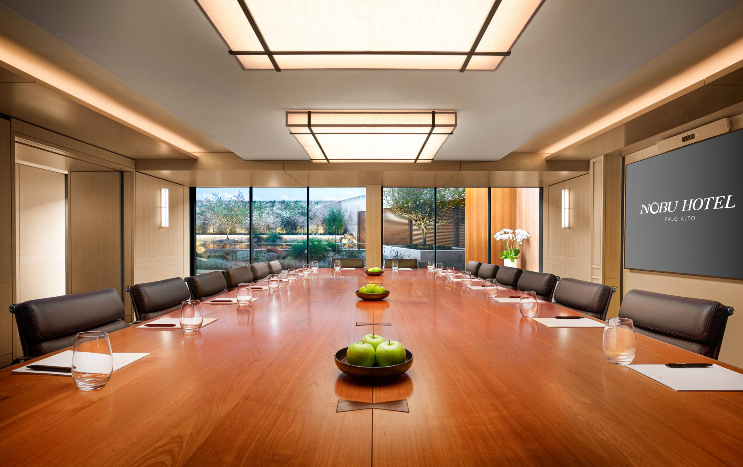 boardroom with conference table, chairs and large windows with garden view