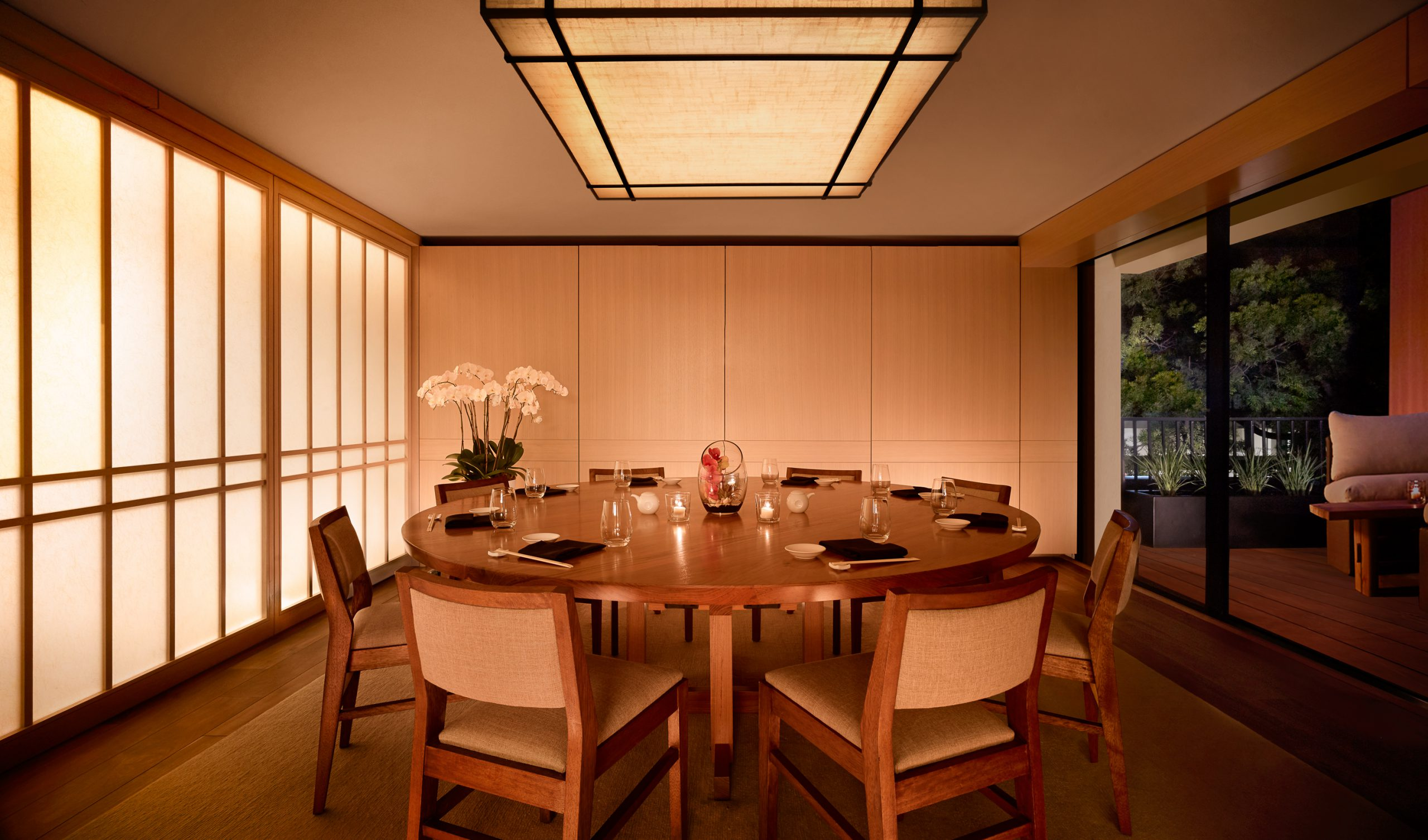 private dining room with round table and glass door to balcony