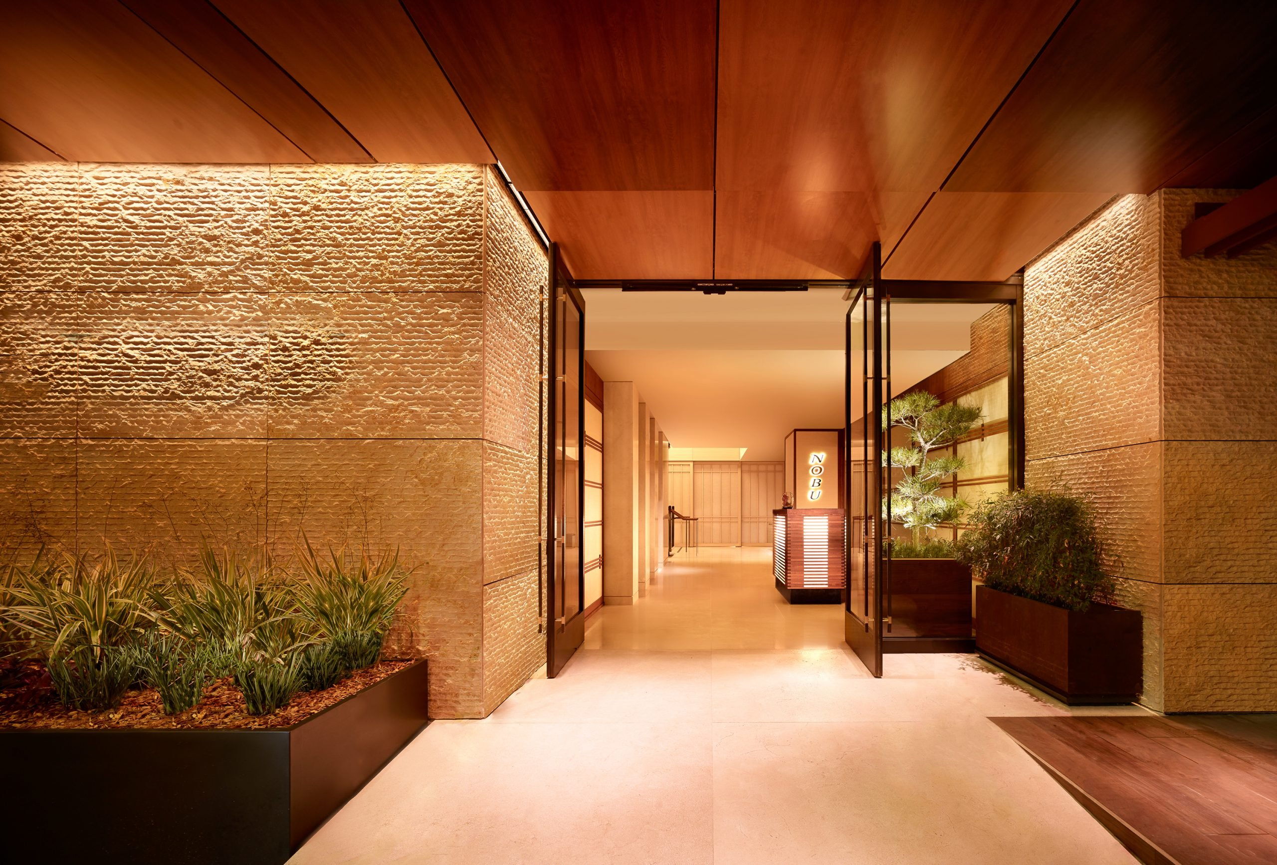 entrance to Nobu with glass doors and wooded ceiling